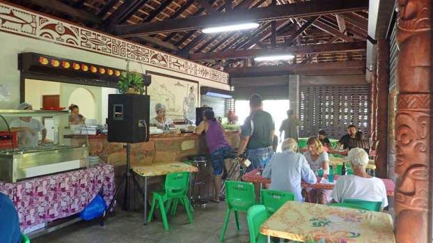 """Cafe Tematapuaua, one of the cruiser hangouts. It's covered and open-sided, so is often cooler than outside. There's this thing called """"coconut time;"""" it's the time from when the sun first hits the coconuts on the trees until it leaves them in shade again. We try to be under cover during """"coconut time"""" as it is the hottest time of the day. This is when we update software, download weather data, update journals and blogs, and catch up with emails and news."""