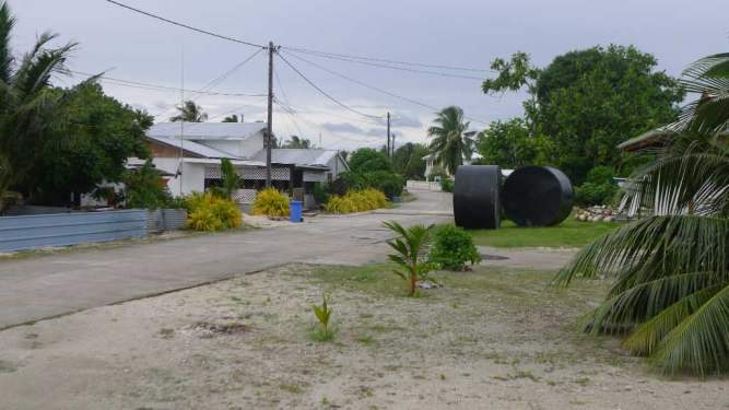 "The main street for the village. Notice the large black tanks; every dwelling has two or more of these above-ground ""cisterns"" to collect rainwater from the roof gutters. Rain water is the only source of water for these dry atolls."