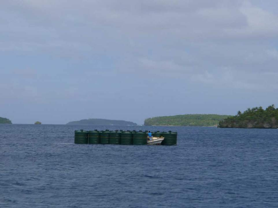 New water cisterns. These were offloaded from the inter island freighter, lashed together, and towed to shore using the small fishing skiff.
