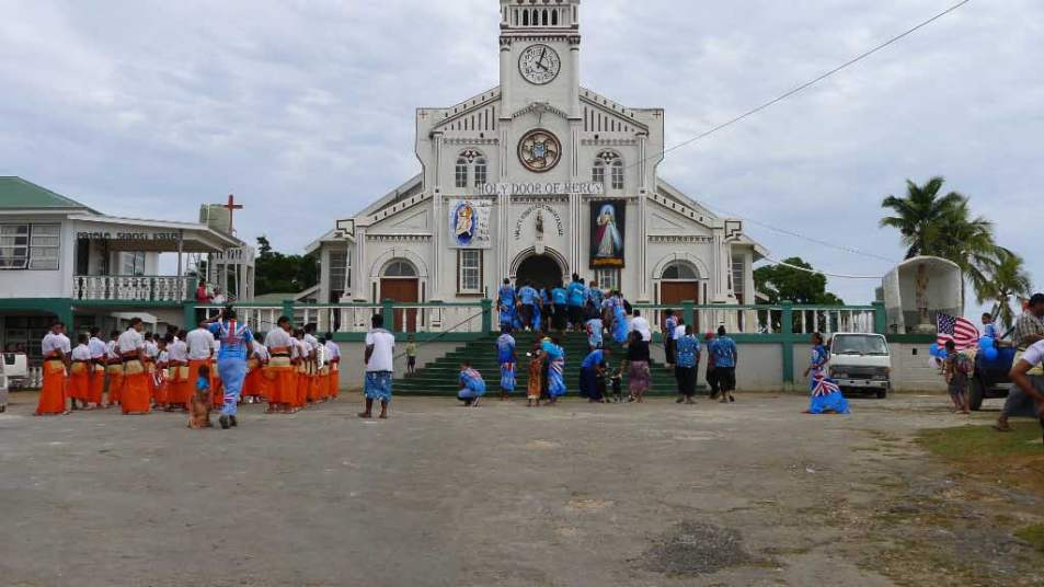 Participants getting blessed. We don't know whether the parade stopped at each church in Neiafu; the photographer just happened to be standing near St. Joseph's so was able to get this shot. This is the church overlooking the harbor and is close enough that we can hear singing from onboard Velic. Lovely.
