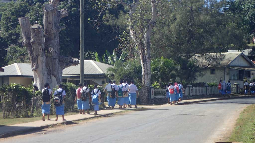 "Schoolboys on their way to classes. Each school has its ""uniform"" color. The boys wear cloth tupenus in their school's colors with a white short sleeve shirt; girls wear cotton jumpers with whites short sleeve blouse. Notice that some of the older boys are wearing woven mat ta'ovalas. Both men and women may wear the woven ta'ovala,"